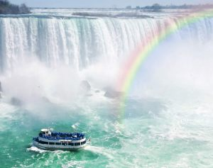 spectacular rainbow near tourist boat at niagara falls